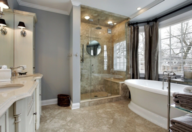 Bathroom with white free-standing tub and tiled walk-in shower with seat