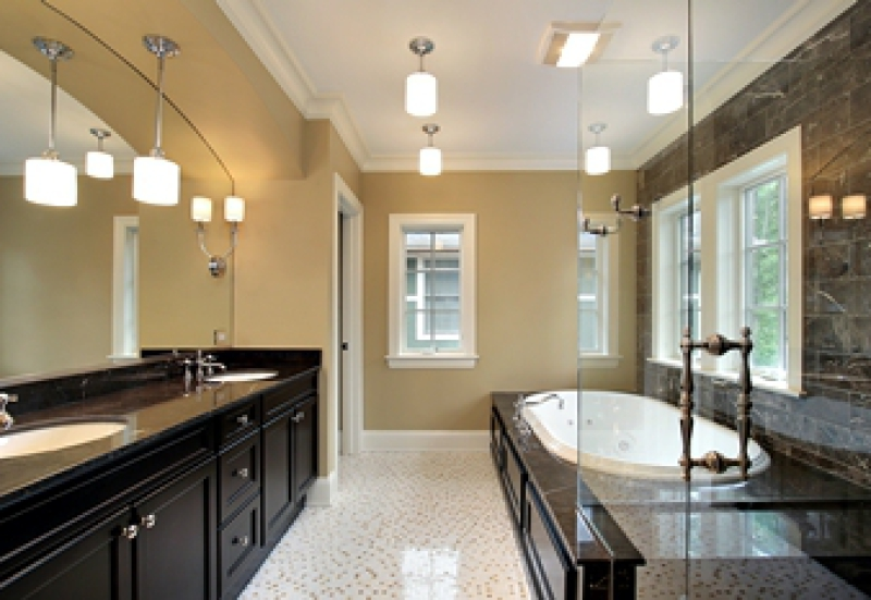 Remodeled bathroom with platform bathtub and dark cabinetry with two sinks